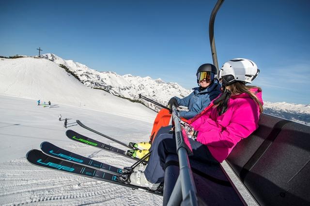 Hymyilevä pariskunta hiihtohississä.
